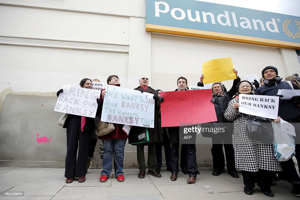 Residents chant slogans and hold signs during a protest next to a section of a wall where celebrated street artist Banksy's 'Slave Labour' graffiti artwork was removed in north London on February 23, 2013. The work that showed a young boy using a sewing machine to make the British flag has been carefully removed and will be auctioned in Miami where it's expected to fetch around 328,000 GBP (500,000 USD). Residents of the North London area have reacted angrily to the removal of the work, but the auction house says the piece was acquired legally.