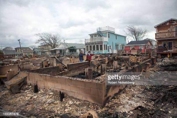 Residents check out the fire damage to their homes after Superstorm Sandy swept through on October 31, 2012 in the Breezy Point neighborhood of the...