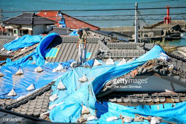Residents check tarps on the roof after Typhoon Hagibis hit past on October 13, 2019 in Tateyama, Chiba, Japan. Ten people died and 12 were reported...