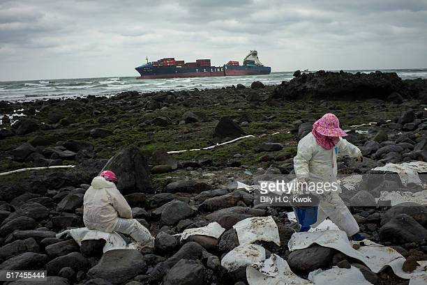 Residents clean a coastal area affected by an oil spill near Taiwan's north coast as a damaged cargo ship lies at the background on March 25, 2016 in...