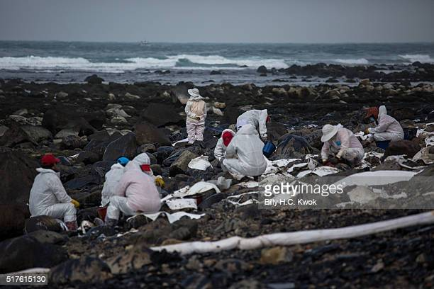 Residents clean a coastal area affected by an oil spill near Taiwan's north coast on March 26, 2016 in Shihmen, Taiwan. An oil slick from a container...