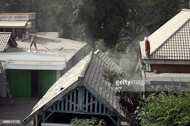 Residents clean ash covered roofs in the village of Kediri in East Java province on February 14 2014 following the eruption of Mount Kelud volcano...