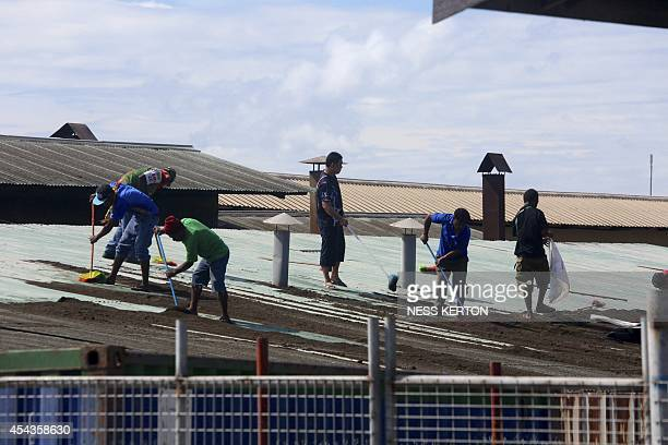 Residents clean ash from their rooftops following the eruption of Mount Tavurvur in eastern Papua New Guinea on August 30 2014 A volcano which has...