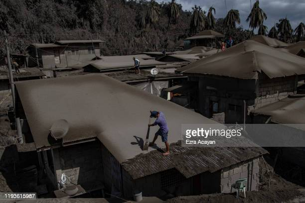 Residents clean rooftops of volcanic ash from Taal Volcano's eruption on January 14 2020 in Laurel Batangas province Philippines The Philippine...