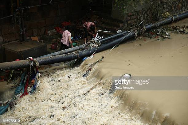 Residents clean the furniture by a river in Bandong Town after Typhoon Nepartak on July 10 2016 in Minqing County Fuzhou City Fujian Province of...