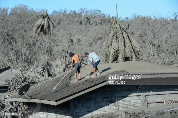 TOPSHOT Residents clean the roof of their home covered in mud and ash due to the eruption of the nearby Taal volcano at a village in Laurel Batangas...