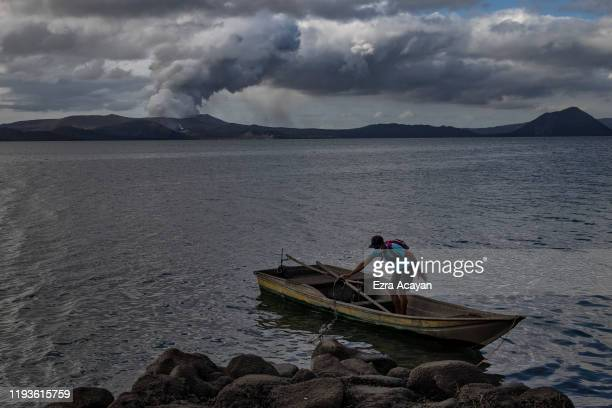 A residents cleans his fishing boat covered in volcanic ash from Taal Volcano's eruption on January 14 2020 in Talisay Batangas province Philippines...