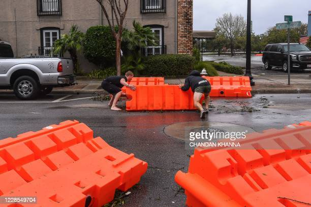Residents clear barricades off a street during Hurricane Sally in downtown Pensacola Florida on September 16 2020 Hurricane Sally barrelled into the...