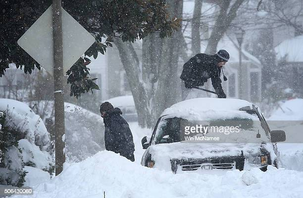 Residents clear snow from their car during a heavy snow fall January 23 2016 in Arlington Virginia Heavy snow continued to fall in the MidAtlantic...