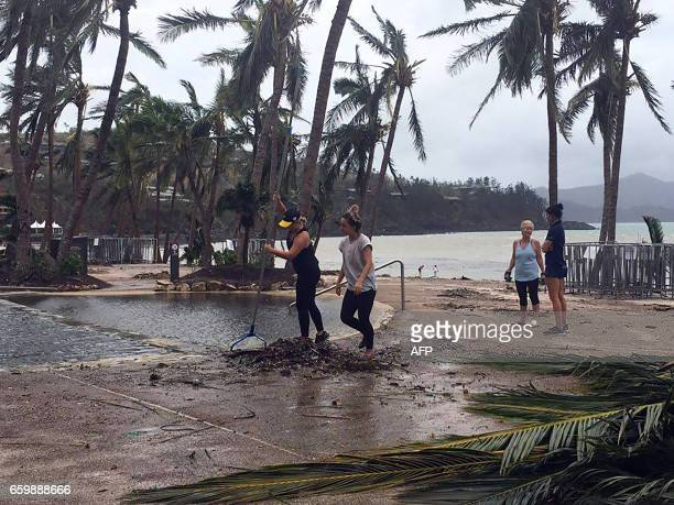 Residents clear the area of fallen trees and branches on the Hamilton Island after strong Cyclone Debbie hit the Whitsundays Islands in Queensland on...
