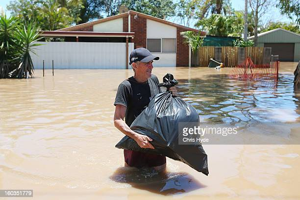 Residents collect belongings from their homes their as parts of southern Queensland experiences record flooding in the wake of Tropical Cyclone...