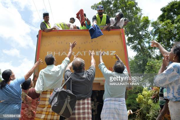 Residents collect food and water from a truck distributing relief materials to those stranded by floods in Pandanad in Alappuzha District in the...