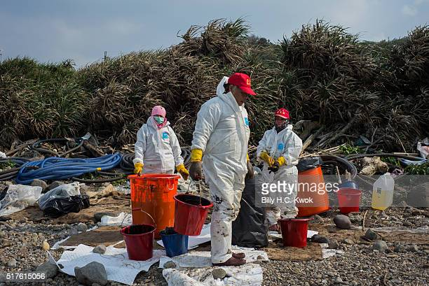Residents collect the oil with buckets in a coastal area affected by an oil spill near Taiwan's north coast on March 26, 2016 in Shihmen, Taiwan. An...