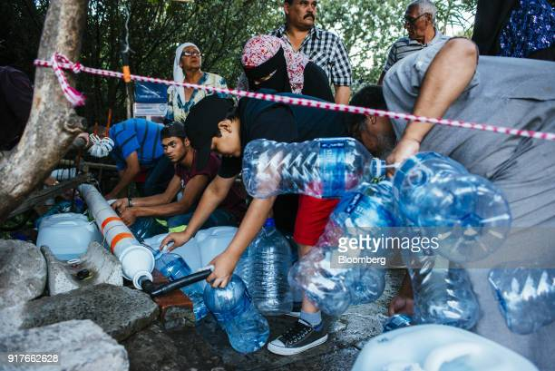 Residents collect water from a pipe to fill plastic water bottles at the Newlands natural water spring in Cape Town South Africa on Wednesday Feb 7...