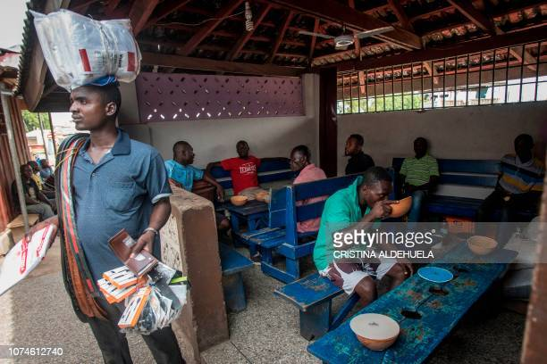Residents consume pito at a joint in Tema Accra on December 12 2018 The price for this local handmade drink is 45 Ghanaian Cedi the equivalent of...