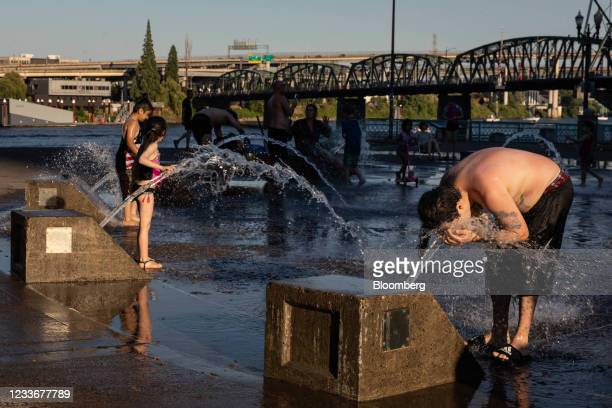 Residents cool off in a riverfront water fountain during a heatwave in Portland, Oregon, U.S., on Saturday, June 26, 2021. Record heat is set to bear...