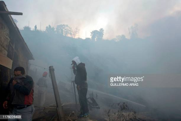 Residents cover from the smoke work to extinguish a fire affecting two houses on a hillside at Camino Verde neighborhood in Tijuana, Baja California...