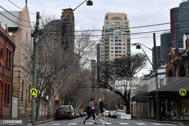 Residents cross an empty intersection in downtown Sydney on July 19 amid a lockdown in Melbourne and Sydney as Australia seeks to contain a surge in...