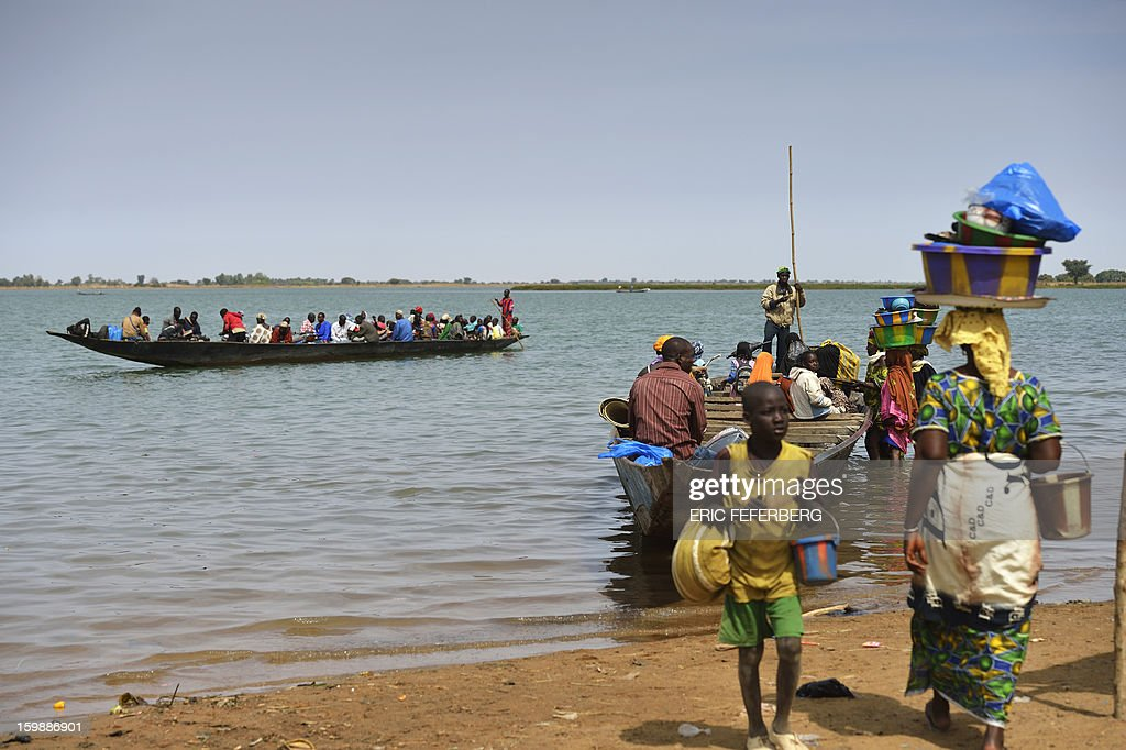 Residents cross the Niger river on a boat on January 22, 2013 near Segou, 240km North of Bamako. Mali's army chief today said his French-backed forces could reclaim the northern towns of Gao and fabled Timbuktu from Islamists in a month, as the United States began airlifting French troops to Mali.