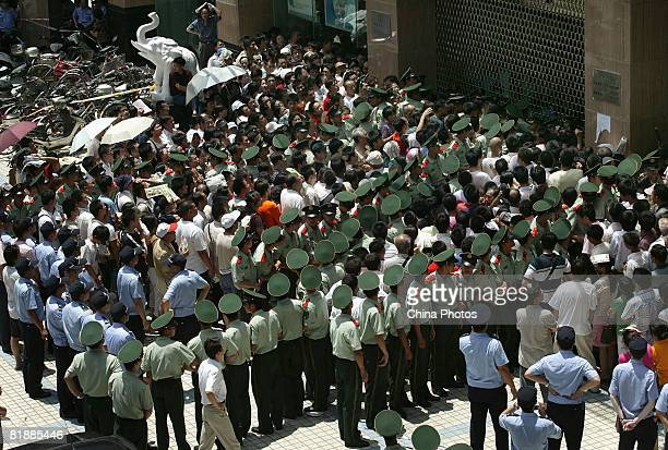 Residents crowd the entrance of a bank to buy new 10-yuan banknote as Chinese paramilitary policemen try to keep order on July 9, 2008 in Nanjing of...