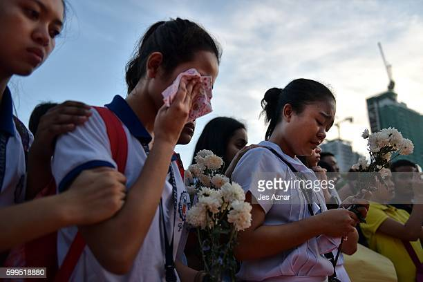 Residents cry as they offer flower and prayers on ground zero of the blast site that killed more than a dozen people in Davao city, on September 5,...