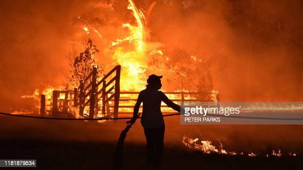 Residents defend a property from a bushfire at Hillsville near Taree 350km north of Sydney on November 12 2019 A state of emergency was declared on...