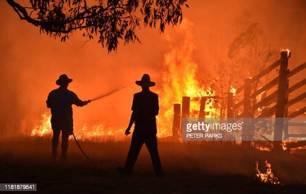 TOPSHOT Residents defend a property from a bushfire at Hillsville near Taree 350km north of Sydney on November 12 2019 A state of emergency was...