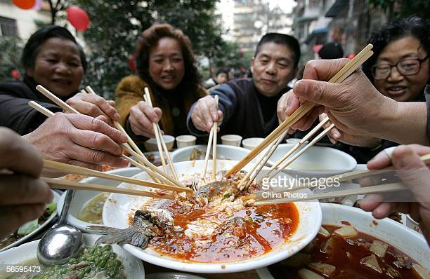 Residents dine on a feast to celebrate upcoming Chinese New Year during a community activity on January 14 2006 in Chengdu of Sichuan Province China...