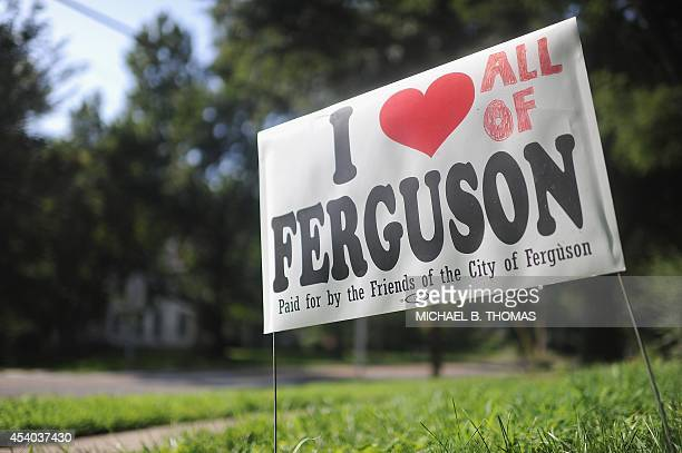 Residents display signs along Elizabeth Avenue in Ferguson Missouri on August 23 2014 as the community prepares to rebuild and heal after the days of...