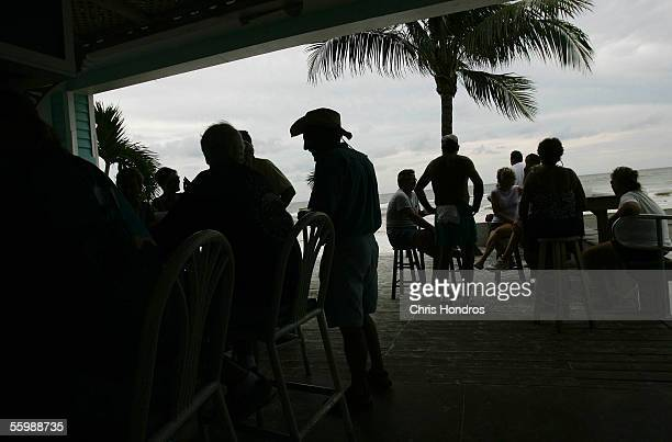 Residents drink at a seaside bar in advance of the arrival of Hurricane Wilma, which is churning in the Gulf of Mexico as a Category 2 storm, October...