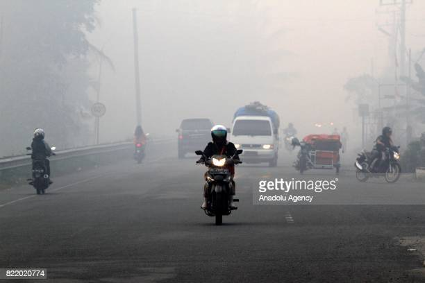Residents drive motorcycle through haze from peat forest fire in Aceh Indonesia on July 25 2017 The number of hotspots in Indonesia continues to...