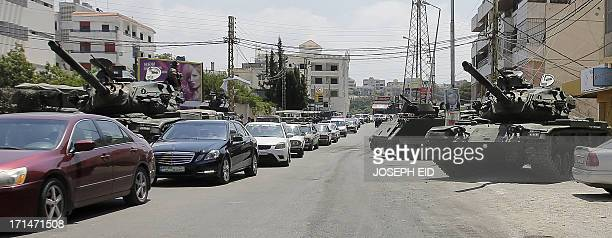 Residents drive past Lebanese army tanks securing the area near the Bilal bin Rabah mosque in the Abra district of the southern city of Sidon on June...