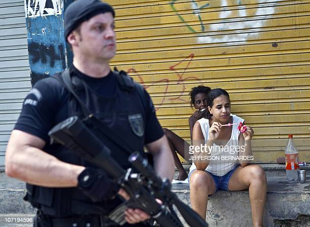 Residents eat icecream as a Coordination of Special Resources policeman patrols Morro do Alemao shantytown on November 29 2010 in Rio de Janeiro...