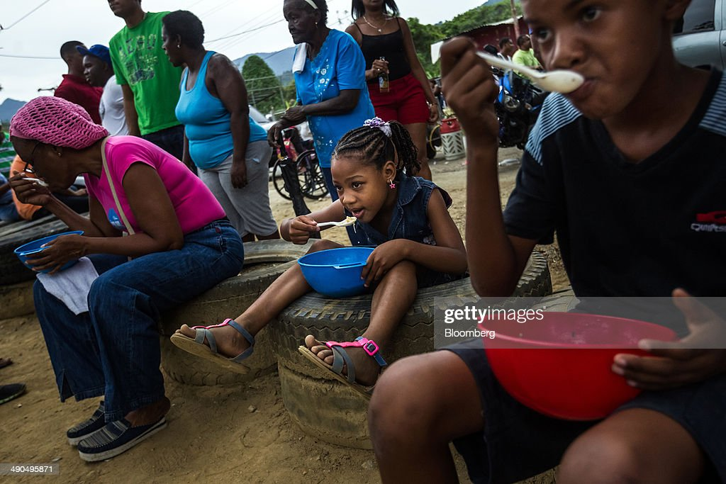 Residents eat soup during a free lunch sponsored by Henrique Capriles, governor of the state of Miranda and a former presidential candidate in the last two elections, during a visit by Capriles, not pictured, in Barlovento, Venezuela, on Saturday, May 10, 2014. Capriles, one of the leaders of the Democratic Unity Roundtable, known as MUD, an alliance which opposes Venezuelan President Nicolas Maduro, said talks with the government scheduled for May 8 were canceled because they 'haven't produced any result up to now.' Photographer: Meridith Kohut/Bloomberg via Getty Images