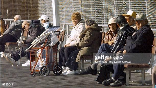Residents enjoy the sun along the boardwalk in Brighton Beach