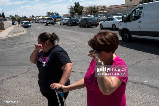 TOPSHOT Residents Erica Rios and Alma Rios cry outside a reunification center at MacArthur Elementary School following a deadly mass shooting in El...