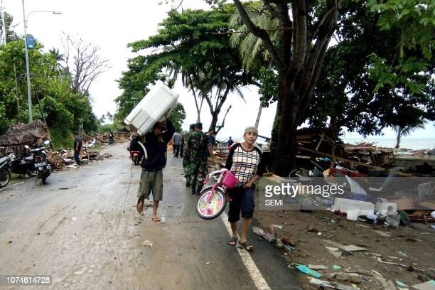 Residents evacuate from damaged homes on Carita beach on December 23 after the area was hit by a tsunami on December 22 that may have been caused by...