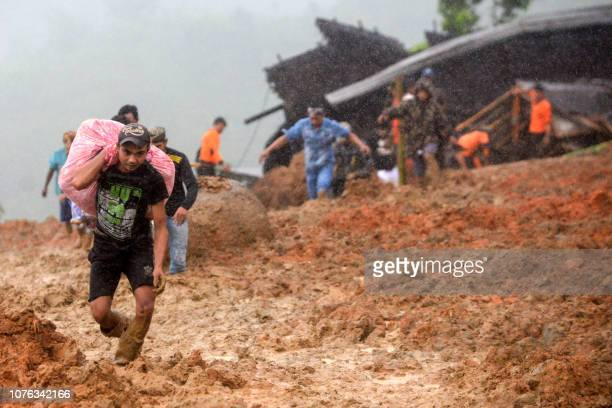 Residents evacuate their homes as rescue workers search for survivors at the site of a landslide triggered by heavy rain in Sukabumi West Java...