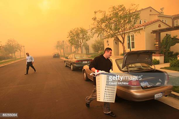 Residents evacuate their homes in the Tuscany development as smoke from the approaching Porter Ranch fire fills the air on October 13 2008 near the...