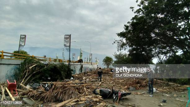Residents examine the tsunami aftermath in Palu on September 29 2018 Rescuers scrambled to reach tsunamihit central Indonesia and assess the damage...