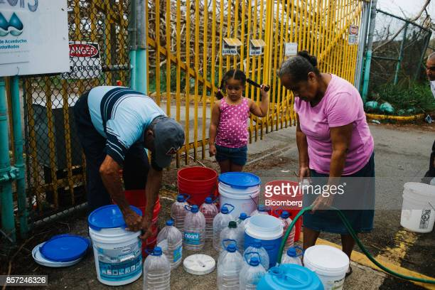 Residents fill containers with water at a center in Rio Grande Puerto Rico on Tuesday Oct 3 2017 US President Donald Trumpvisited stormravaged...