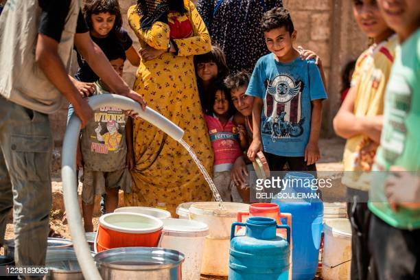 Residents fill up water from cisterns provided by humanitarian organisations during a water outage in Syria's northeastern city of Hasakah on August...