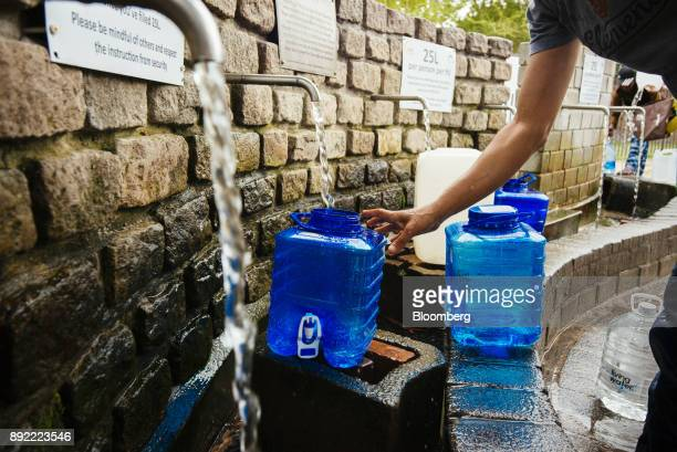 Residents fill water bottles and containers at the Newlands natural water spring in Cape Town South Africa on Monday Nov 13 2017 Cape Town has...