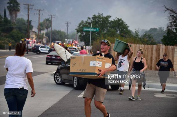 Residents flee a neighborhood with their belongings after a spot fire broke out at the Holy Fire in Lake Elsinore California southeast of Los Angeles...