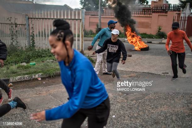 Residents flee incoming rubber bullets fired by South African police officers in the street of Johannesburg on April 23 2019 during a protest against...