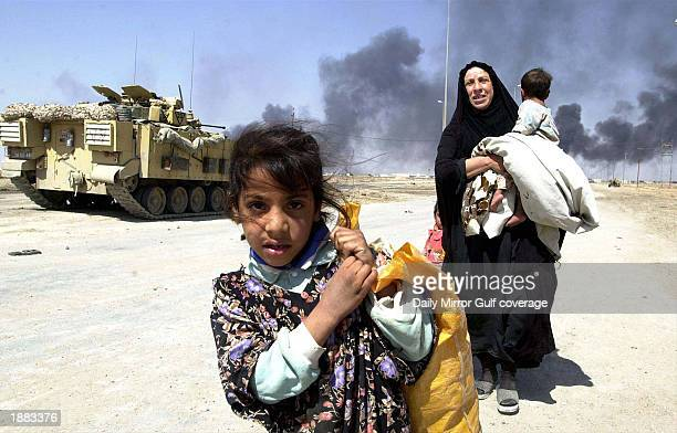 Residents flee the burning town of Basra March 28, 2003 in Iraq. U.S. Bombing continues as coalition forces carry out an operation to oust Iraqi...