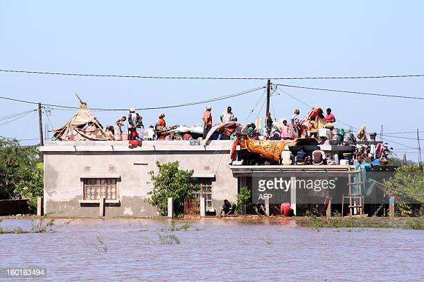 Residents flee to the roof of a house in Chokwe district to escape the floods on January 25 2013 The death toll from heavy flooding in Mozambique...