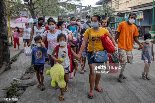 Residents fleeing Taal Volcano's eruption arrives at an evacuation center on January 13 2020 in Santo Tomas Batangas province Philippines The...