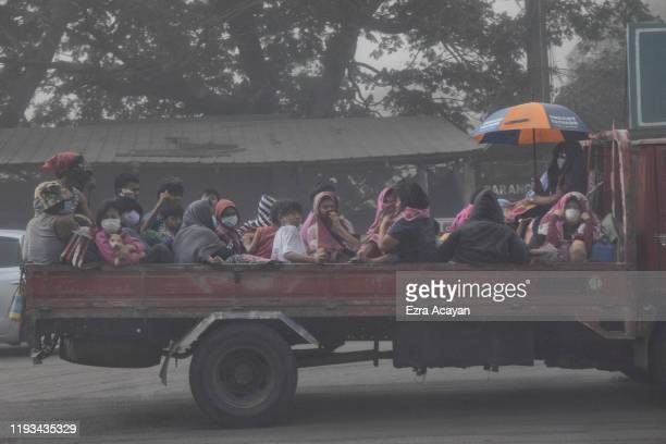 Residents fleeing Taal Volcano's eruption ride a flatbed truck on January 13 2020 in Lemery Batangas province Philippines The Philippine Institute of...