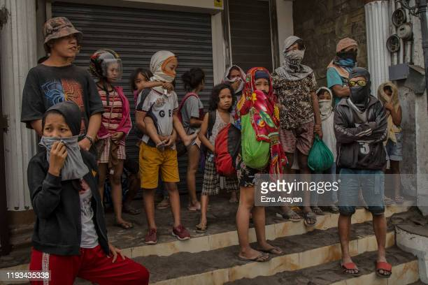 Residents fleeing Taal Volcano's eruption wait for a ride on the side of a highway on January 13 2020 in Lemery Batangas province Philippines The...